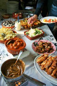 Tapasfeestje een mooie tapastafel of tapasbuffet met lekkere tapas in hele mooie tapasschalen - kip met spek - Spaanse aardappelsalade - Spaanse gehaktballetjes - een hand die opschept - mels Feestje en 8x Tapasfeestje