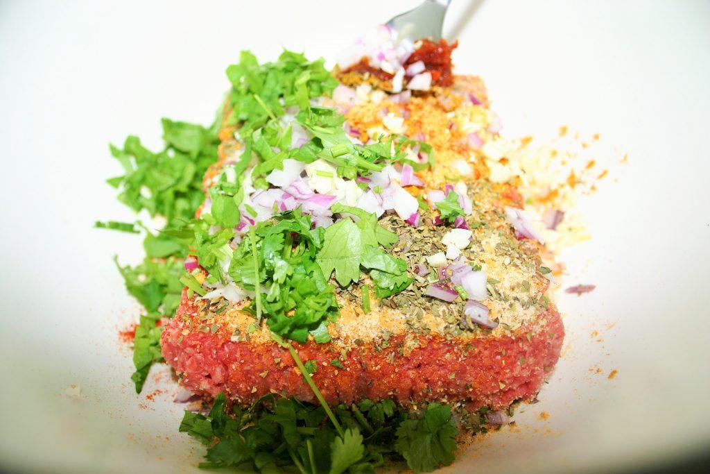 Ingergredienten voor de overheelrijk gemarineerde hamburger met ui knoflook verse koriander een plak cheddar kaas op een Italiaanse bol - Mels Feestje en Feest hapjes