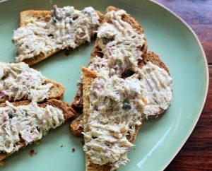 Heerlijke geroosterde broodjes met knoflookboter - Daarop een makreelsalade met mayonaise truffel kappertjes en rode ui - Broodjes met de makreelsalade op een bord om vanaf te pakken - Mels Feestje